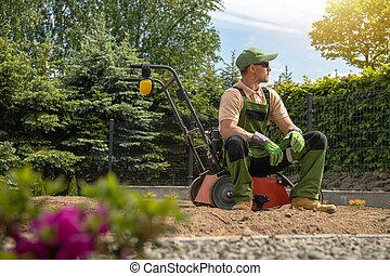 Gardener Relaxing After Backyard Lawn Aeration