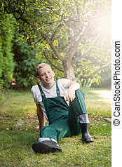 Gardener sitting on the grass - Gardener in dungarees...