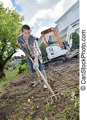Gardener using a rake