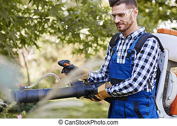 Gardener using leaf blower at garden