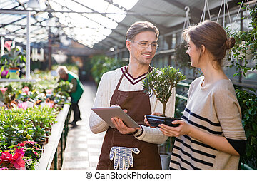 Gardener using tablet and talking with woman holding bonsai tree