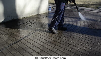 gardener with jet of water wash away trash from the tile.