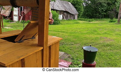 gardener water bucket - Gardener man at well house take...