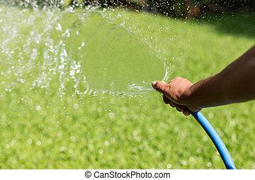 Gardener watering garden from hose