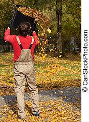 Gardener with bucket full of leaves