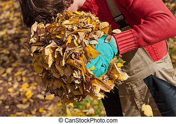 Gardener with pile of leaves