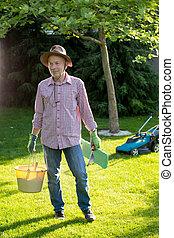 Gardener with tools in backyard