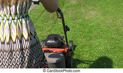 Gardener woman in spotty dress push lawn mower cutting...
