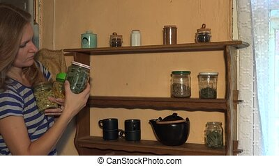 Gardener woman make healthy dried herb plants reserve for winter time.