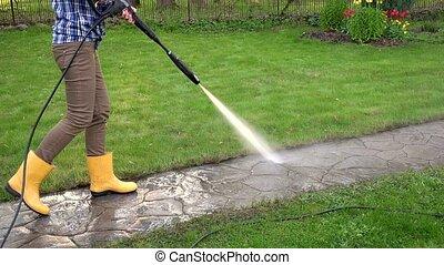 Gardener woman washing footpath with high pressure water jet.