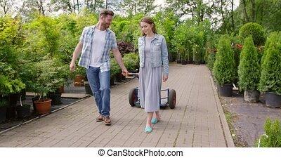 Gardeners pulling wagon - Horizontal outdoors shot of male...