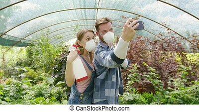 Gardeners taking selfie with respirator - Male and female...
