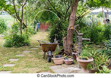 Gardening - Beautiful Residential Backyard Garden in the vilage, Equipment For Gardener With Flowerpots, Wheelbarrow and Water Pump.