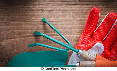 Gardening gloves trowel and rake on wooden surface