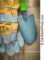 Gardening hand spade protective gloves on wooden board