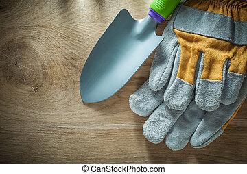 Gardening hand spade safety gloves on wooden board