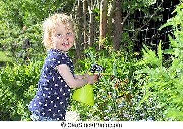 Happy child in garden sprays roses