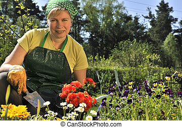 gardening - happy woman with flowers in her garden