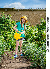 Gardening - nice girl watering plants in the garden