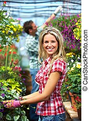Gardening people. Couple working in greenhouse with flowers.