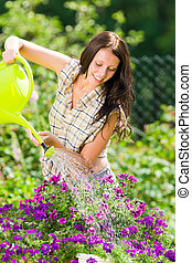 Gardening smiling woman watering can violet flower - Summer...