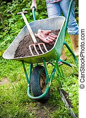 Gardening - gardener with a wheelbarrow full of humus in the...