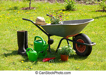 Gardening tools and a straw hat on the grass in the garden
