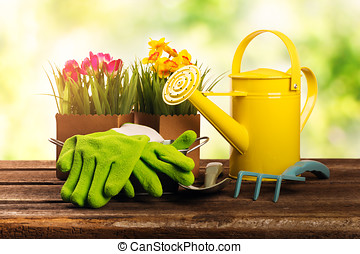 gardening tools and flowers on old wooden table in garden