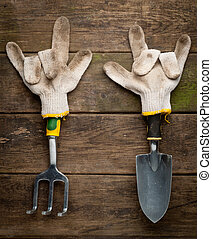 Gardening tools in working gloves on wooden