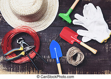 Gardening tools on dark wooden background with pliers , straw hat , rope , gloves trowel garden equipment