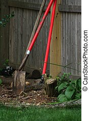 Gardening Tools on fence - several garden tools leaning upon...