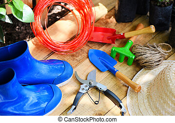 Gardening tools on wooden board with pruning shears rope rubber boot garden trowel equipment and straw hat