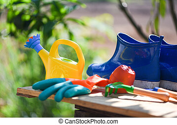 Gardening tools on wooden board with rubber boot garden gloves trowel equipment and watering can at back yard