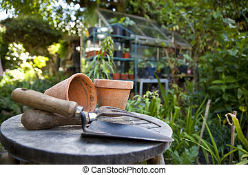 Gardening utensils and flower pots resting on a stool in a green garden with a greenhouse out of focus in the background