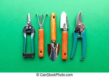 Gardening utensils on green background