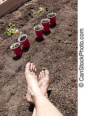 Gardening with feet in the dirt.