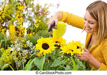 Gardening - woman sprinkling water to sunflowers