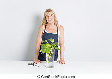 Gardening woman with plant. Isolated on white background.