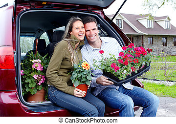 Gardening. - Young smiling couple with flowers near home.