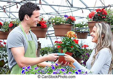 Gardening. - Young smiling seller florist working in flower...