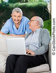 gardien, ordinateur portable, divan, utilisation, homme aîné
