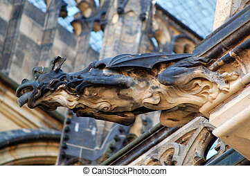 Close-up of gargoyle figure, Europe. In architecture, a gargoyle is a carved stone grotesque with a spout designed to convey water from a roof and away from the side of a building.