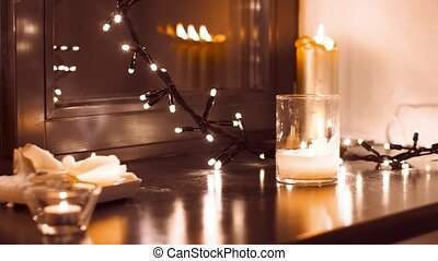 garland and candles burning on window sill at home - hygge,...