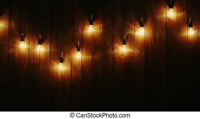 Garland of electric bulbs on a wooden background
