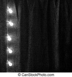 Garland of light bulbs hanging verticaly in the dark room.