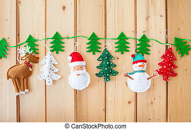 Garland with felt christmas decorations on rustic wooden...
