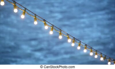 Garland with illumination on deck of ship which floats in sea