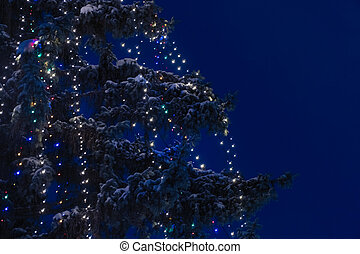 Garland with lights on a snow-covered Christmas tree at night