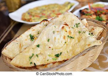 Garlic and coriander naan on a basket. Indian food.