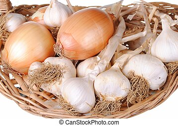 Garlic and onions in a straw basket, isolated on white